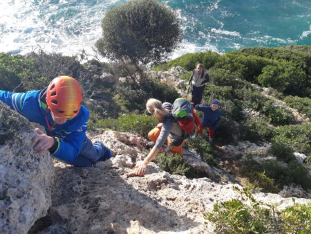 Nils Helsper (RP1, left) managing a short free solo climb on the way back to the car after climbinging in Cala Bota (Mallorca, Spain), Anna Lipp (AU1, right side on the ground) waiting for her turn to climb up with just one arm.